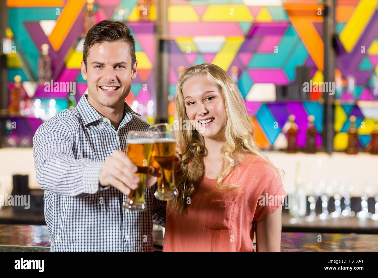 Couple showing a glass of beer in bar - Stock Image