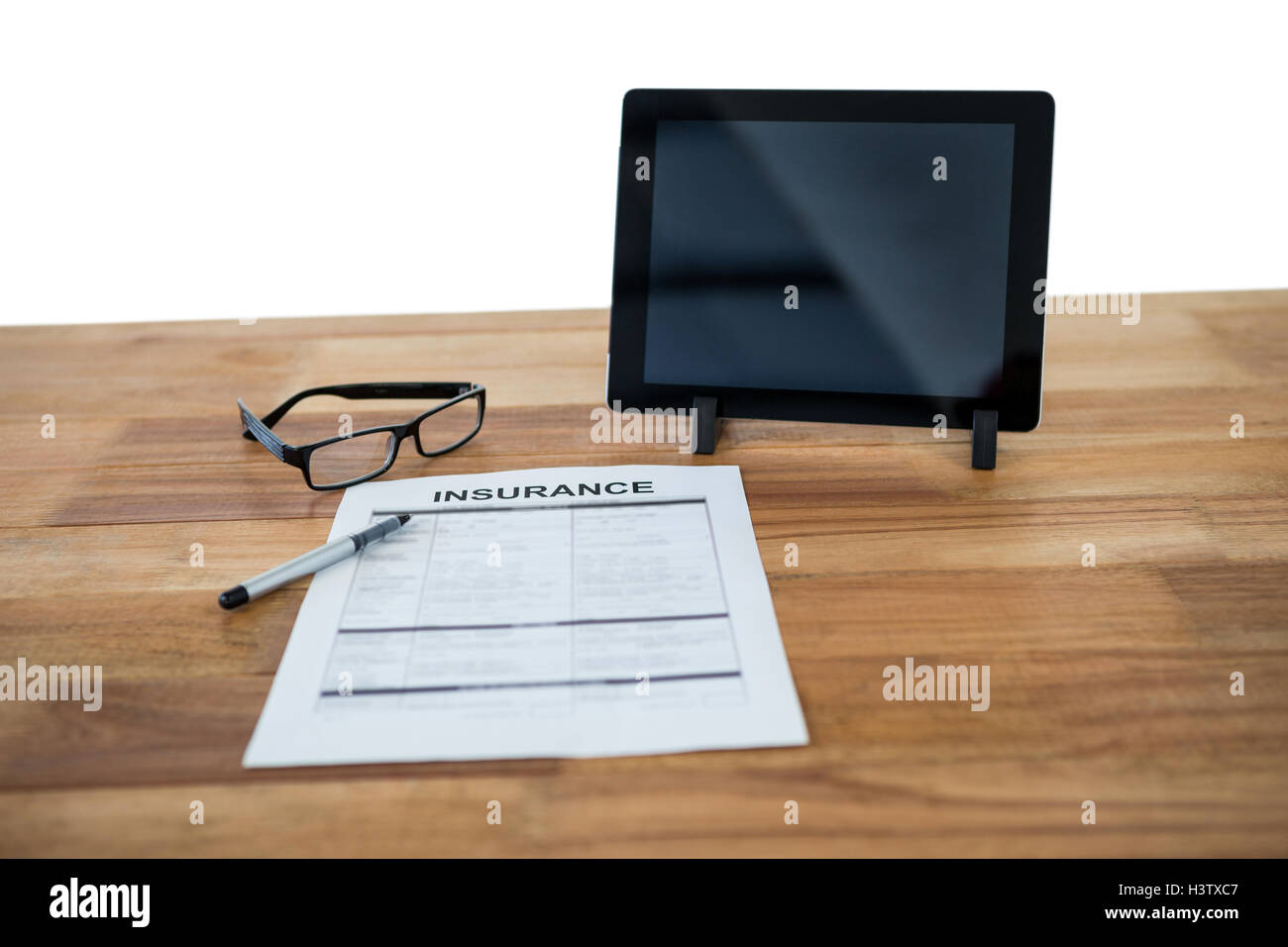 Digital tablet, insurance form, spectacle and pen on desk - Stock Image