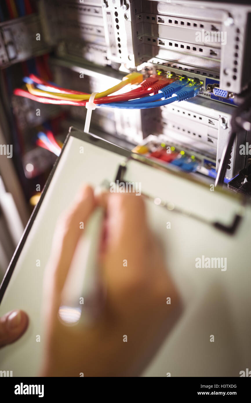 Technician maintaining record of rack mounted server on clipboard - Stock Image