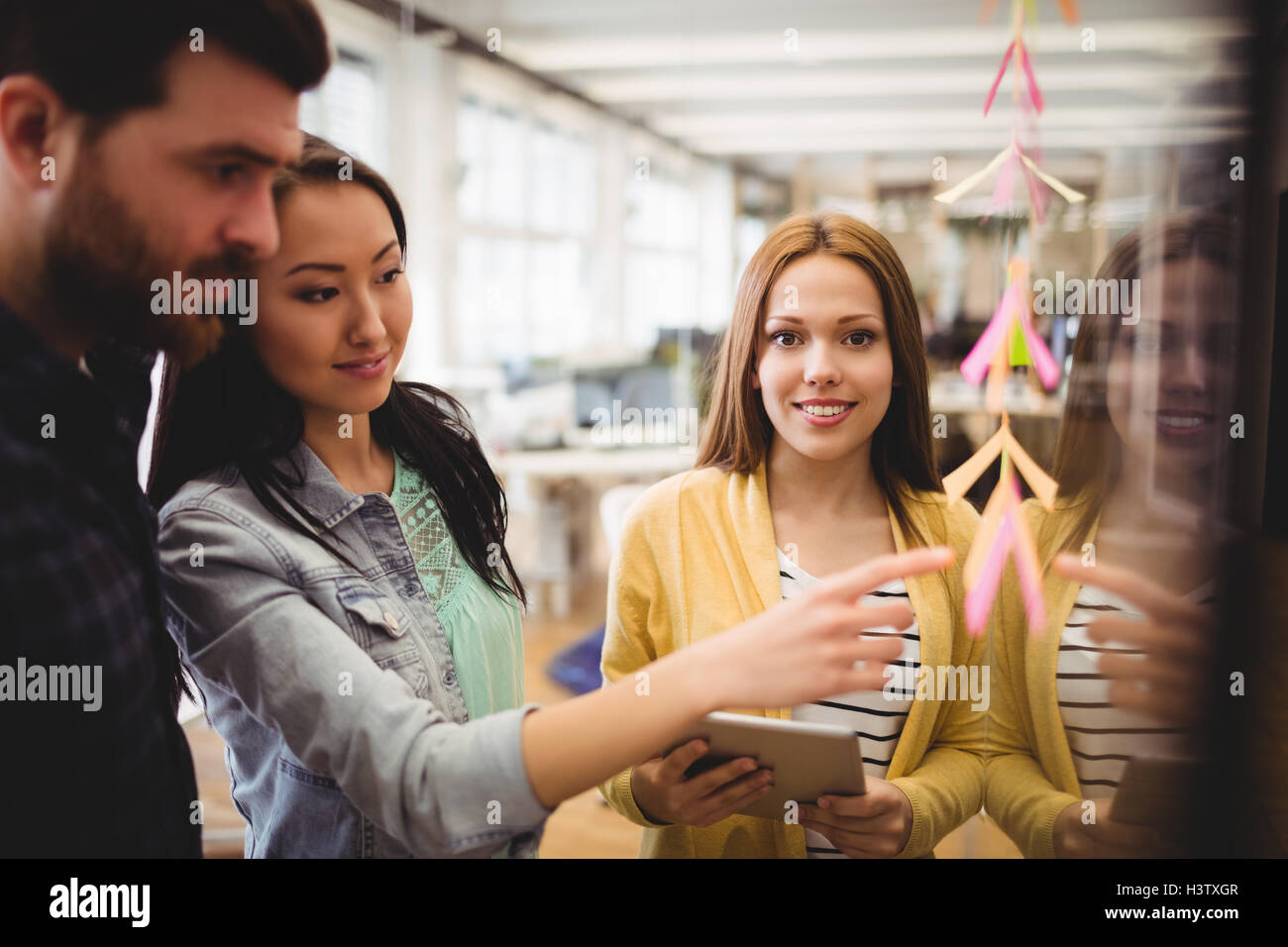 Female photo editor standing near coworkers pointing on sticky note - Stock Image