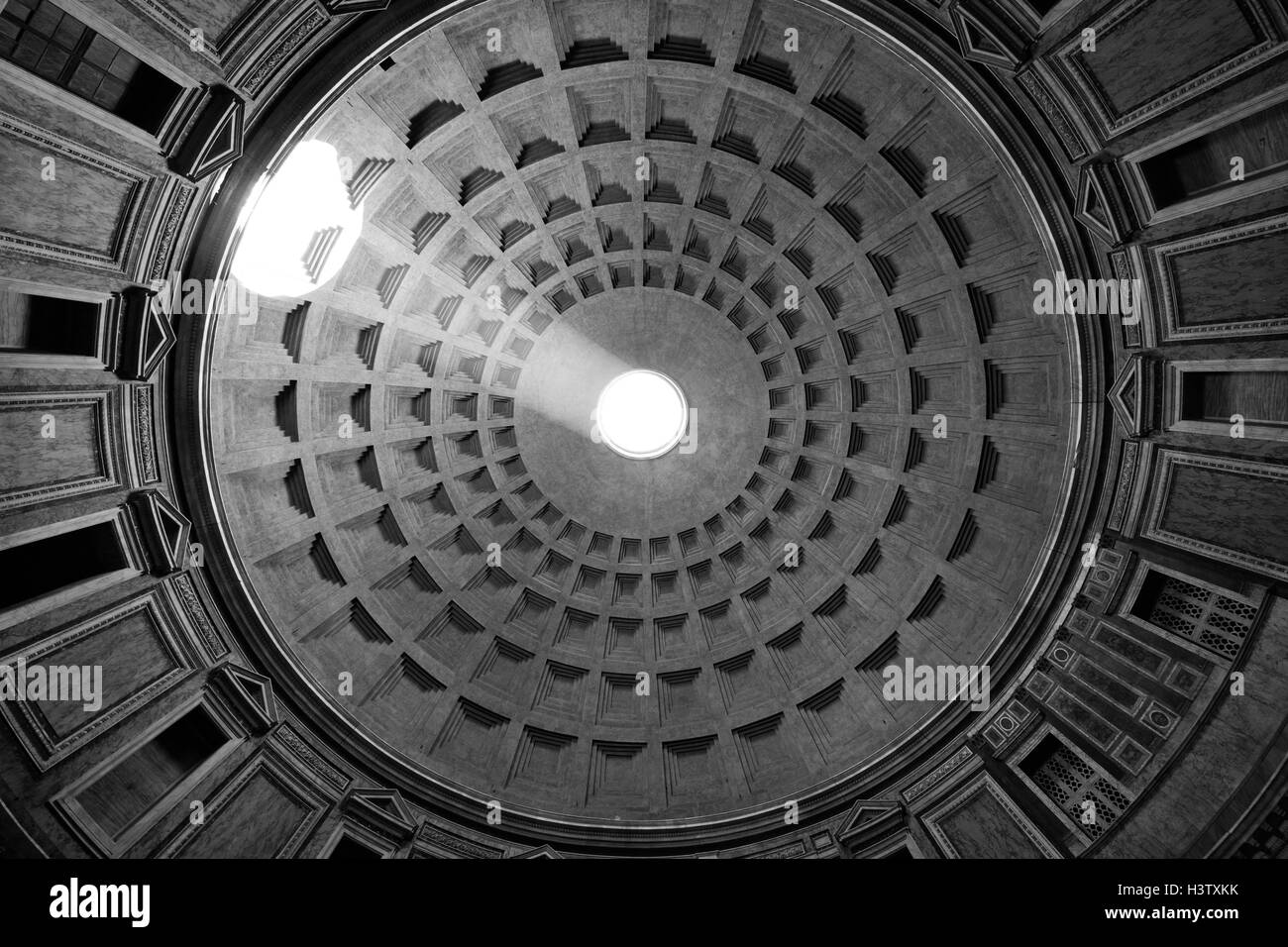 The sun illuminates the inside of the ceiling through the hole at the top of the Pantheon in Rome, Italy - Stock Image