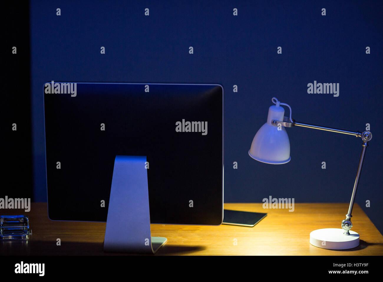 Close-up computer monitor and illuminated lamp - Stock Image