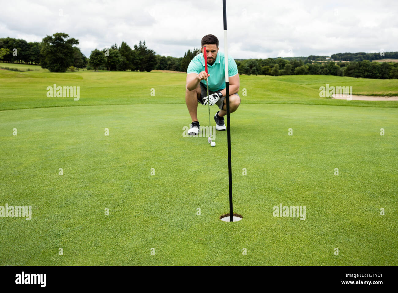 Man squatting to line up his putt - Stock Image