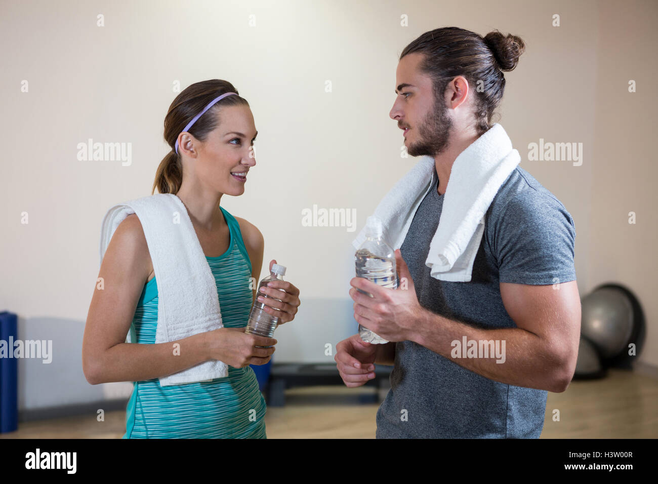 Fitness trainer and woman holding water bottle - Stock Image