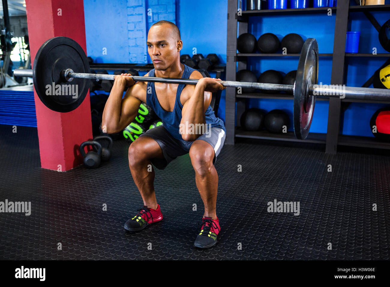 Male athlete weightlifting in fitness studio - Stock Image