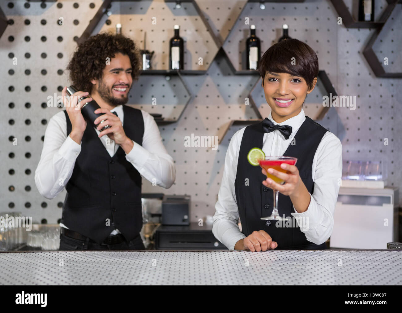 Two bartenders preparing cocktail and serving in bar counter - Stock Image
