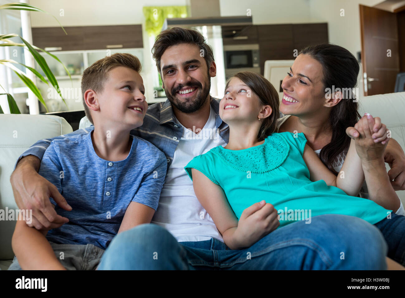 Happy family sitting with arm around on sofa - Stock Image
