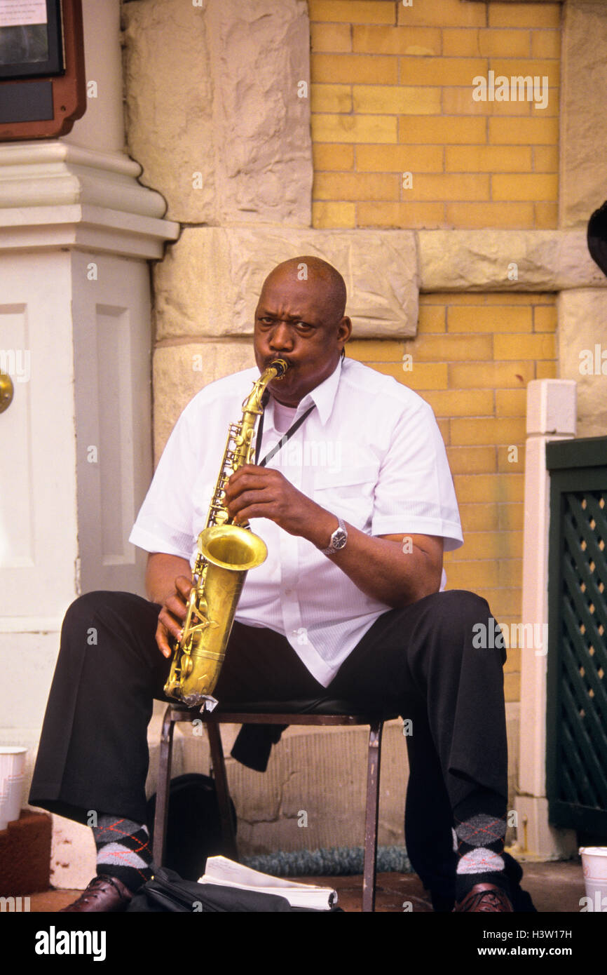 1990s STREET MUSICIAN PLAYING A SAXOPHONE ON A CORNER LOOKING AT CAMERA - Stock Image