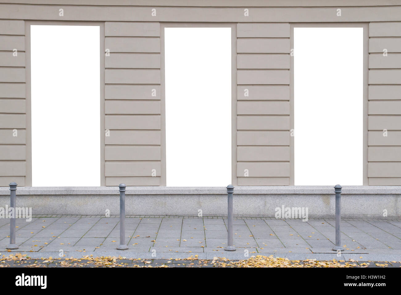 Three blank vertical mockups on a building wall. Autumn street. Front view Stock Photo