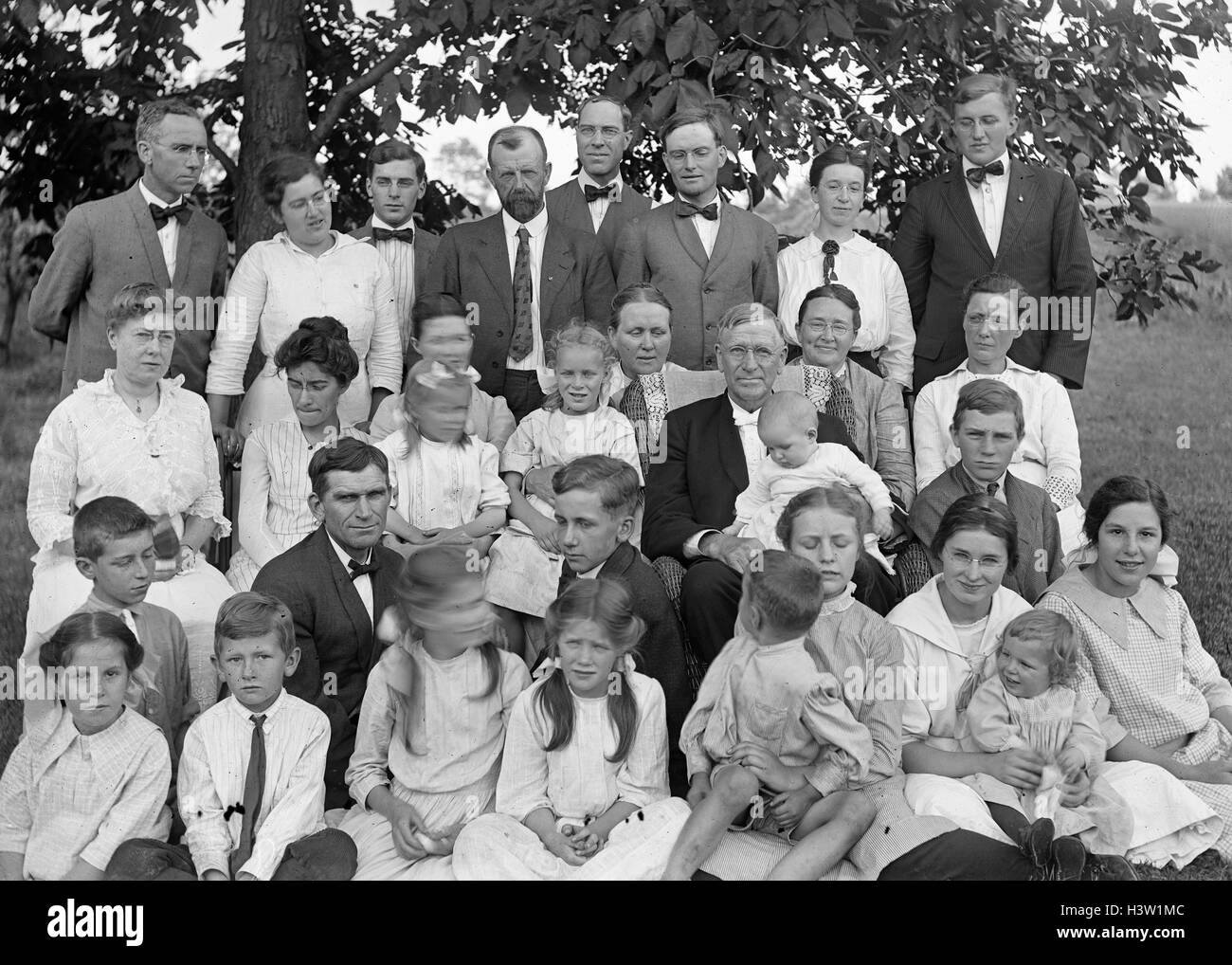 1900s 1915 GROUP PORTRAIT EXTENDED FAMILY THREE GENERATIONS OUTDOORS ON LAWN LOOKING AT CAMERA - Stock Image