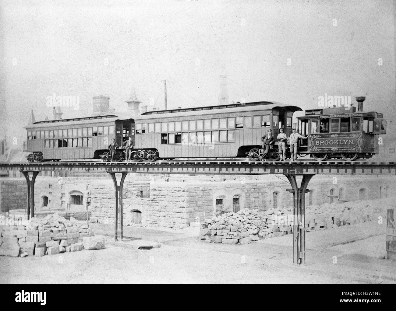 1880s 1890s STEAM ENGINE AND TWO PASSENGER CARS ON THE EL ELEVATED TRAIN TRACKS IN BROOKLYN NEW YORK USA - Stock Image