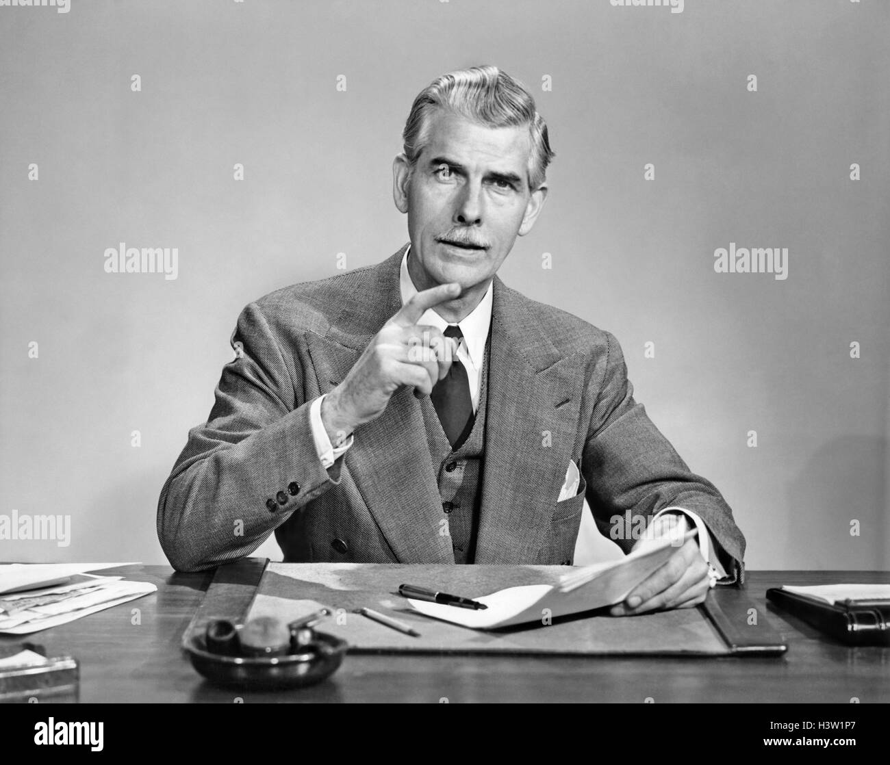 1950s SENIOR GRAY HAIRED BUSINESS EXECUTIVE WITH MUSTACHE SEATED AT DESK HOLDING PAPER GESTURING WITH FINGER LOOKING - Stock Image