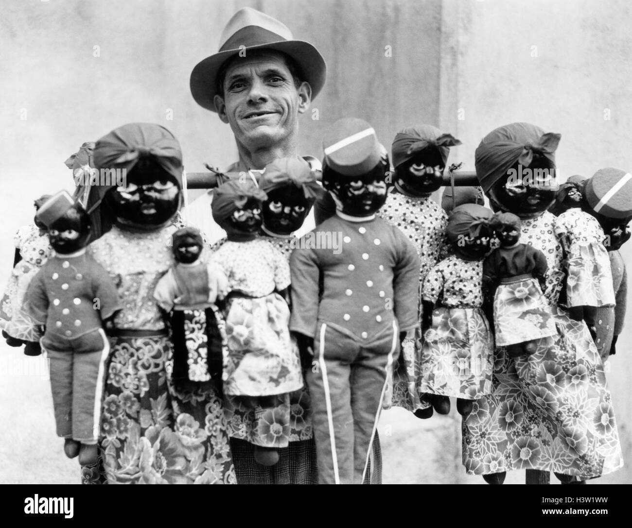 1930s 1940s WHITE STREET VENDOR LOOKING AT CAMERA SELLING BLACK FACED DOLLS HAVANA CUBA - Stock Image