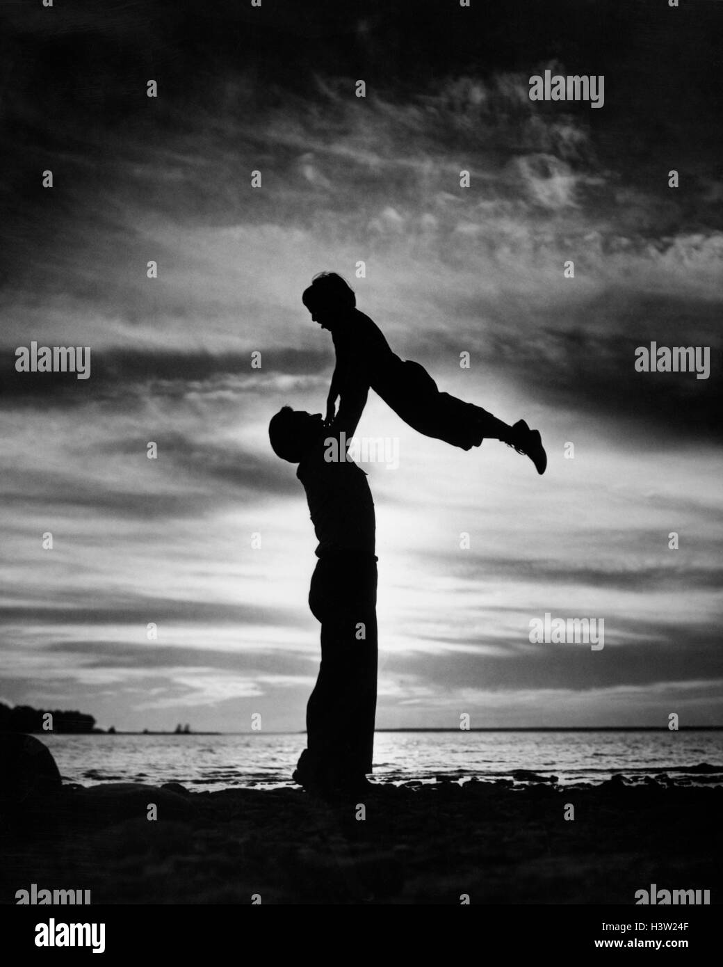 1940s 1950s ANONYMOUS SILHOUETTED MAN FATHER LIFTING CHILD SON IN AIR ON SHORE AT DUSK - Stock Image