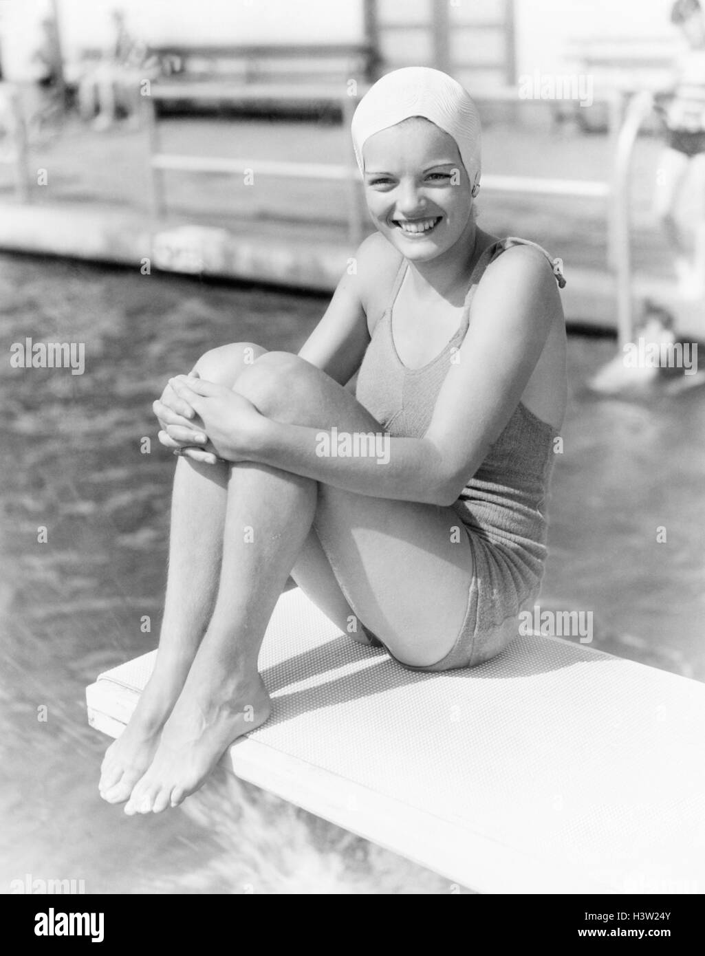 1930s GIRL WEARING BATHING SUIT AND SWIM CAP SITTING ON DIVING BOARD HOLDING KNEES LOOKING AT CAMERA - Stock Image
