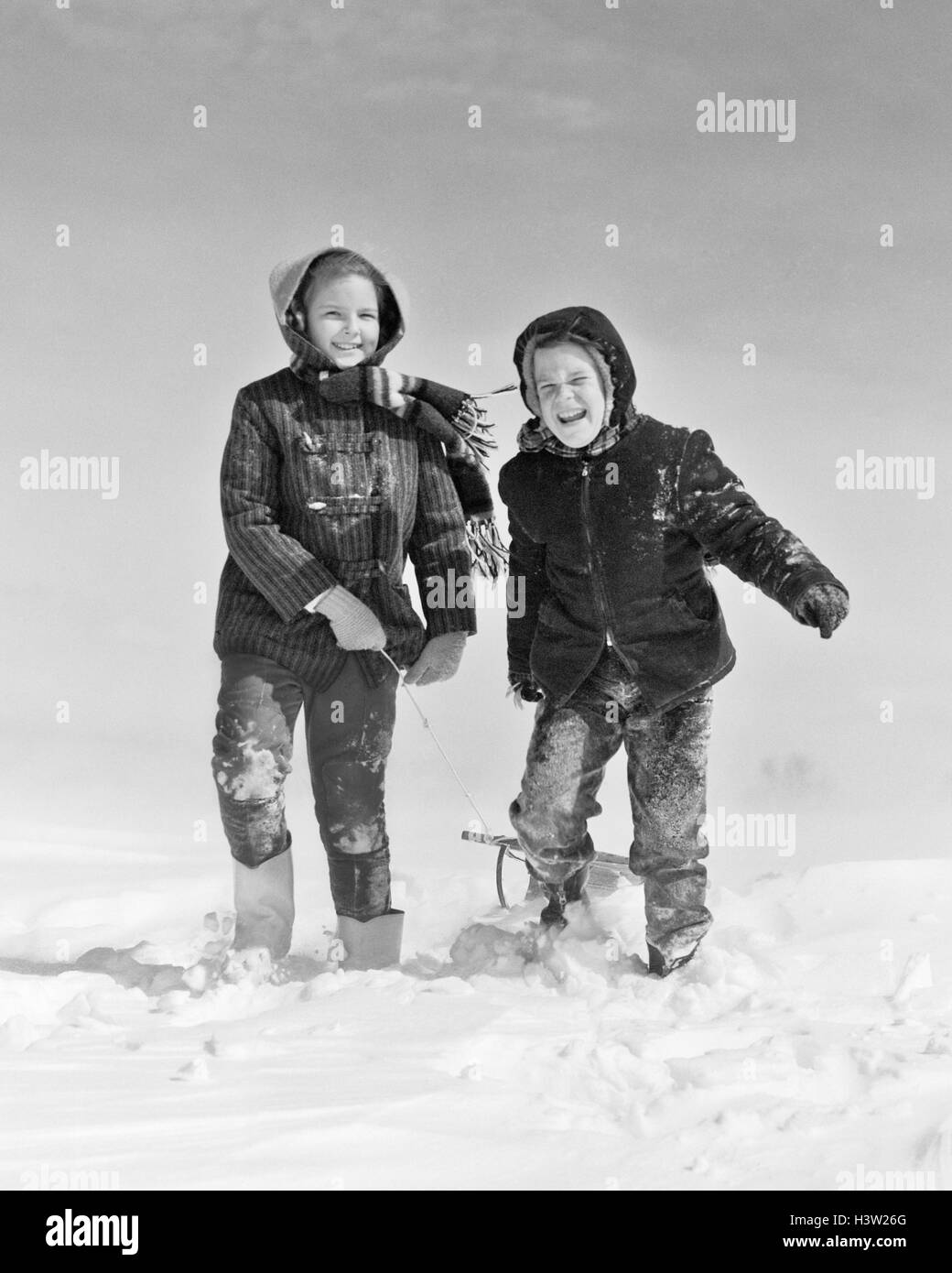 1950s 1960s SMILING BOY GIRL PULLING SLED IN WINTER SNOW - Stock Image