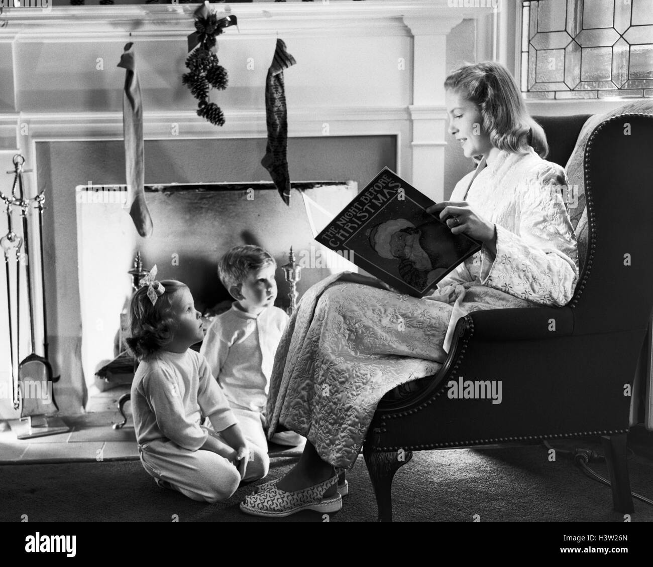 1940s 1950s MOTHER READING CHRISTMAS STORY TO BOY GIRL SITTING BY FIREPLACE HUNG WITH STOCKINGS - Stock Image