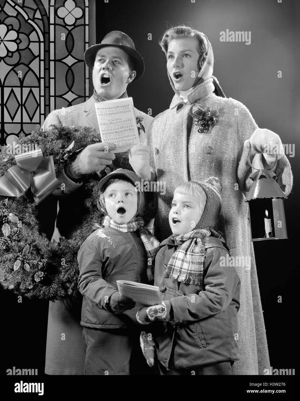 1950s FAMILY OF FOUR SON DAUGHTER SINGING CHRISTMAS CAROLS DAD HOLDING WREATH MOM HOLDING CANDLE LANTERN - Stock Image
