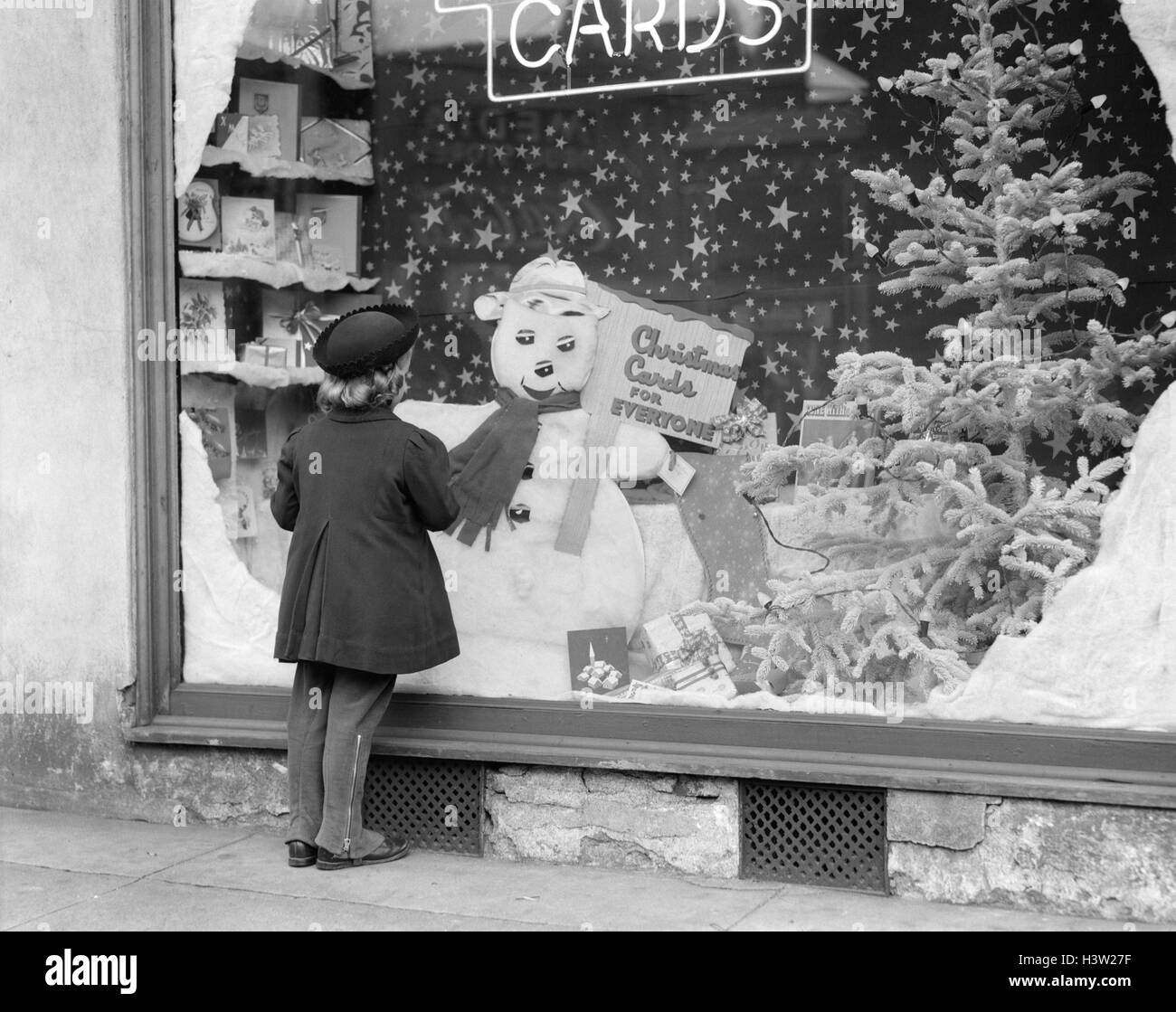 1930s 1940s LITTLE GIRL LOOK INTO CARD SHOP WINDOW WITH CHRISTMAS DECORATIONS AND SNOWMAN DISPLAY Stock Photo