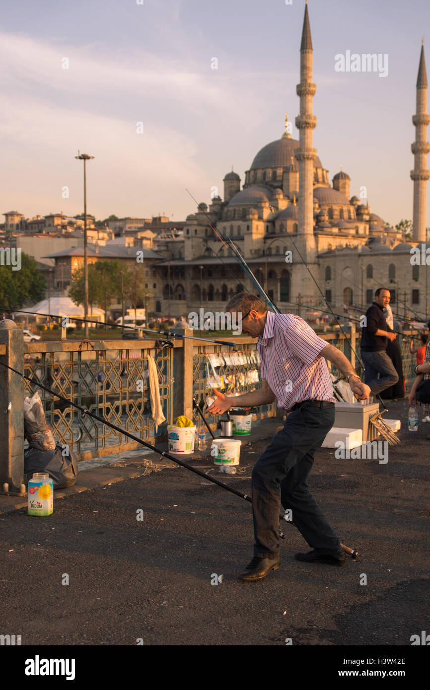 Fisherman trying to steady the fish that he had just caught (near his left foot), in Istanbul (Turkey) - Stock Image