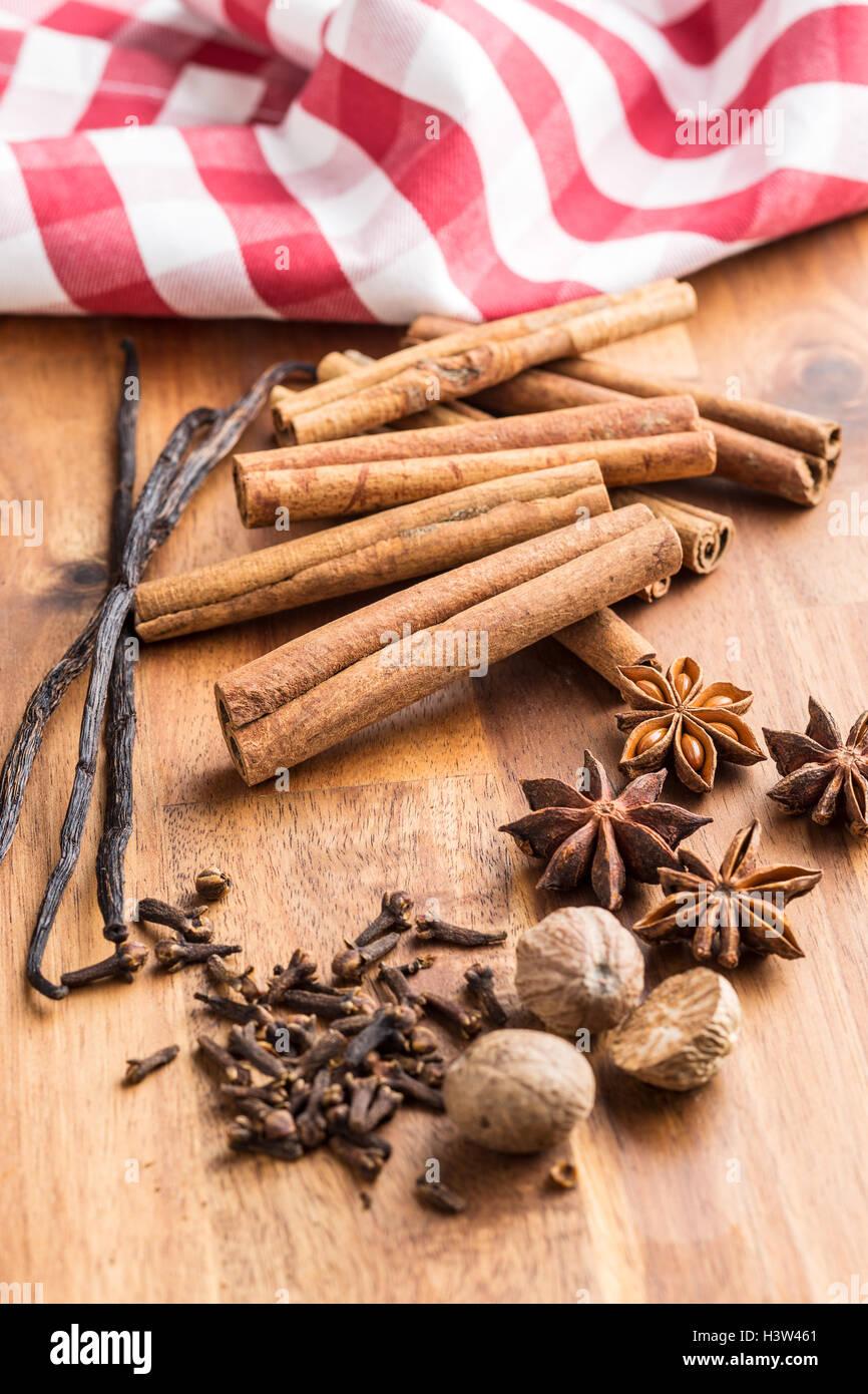 Vanilla, cinnamon, clove, nutmeg and anise star on wooden table. - Stock Image