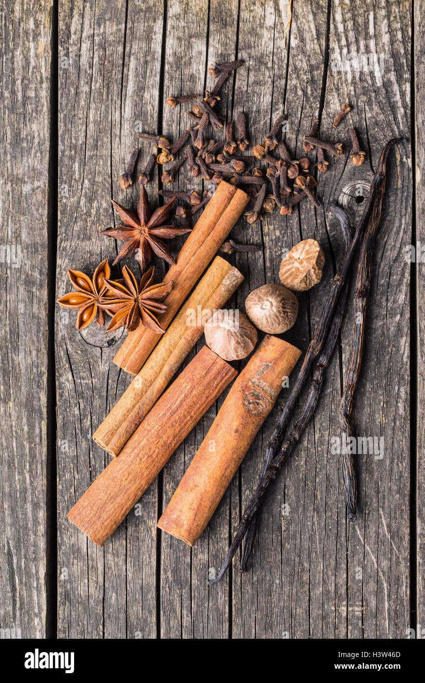 Vanilla, cinnamon, clove, nutmeg and anise star on old wooden table. - Stock Image