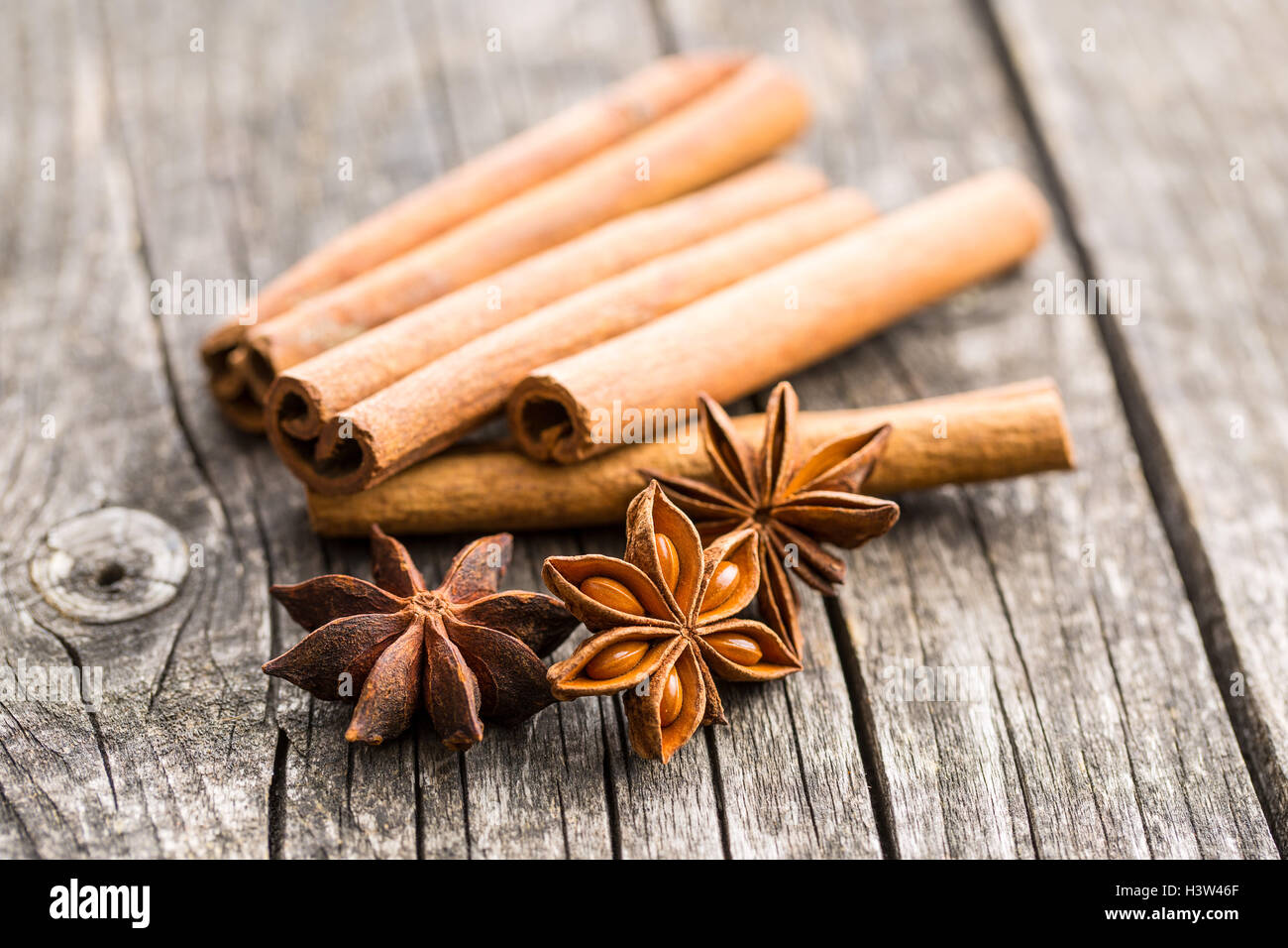 Cinnamon sticks and anise stars on old wooden table. - Stock Image
