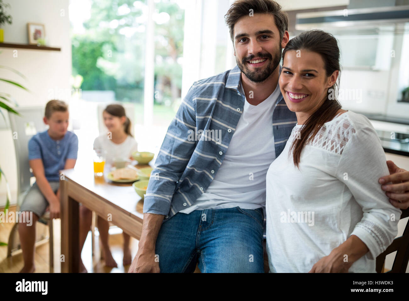 Portrait of couple sitting with arm around on dining table - Stock Image
