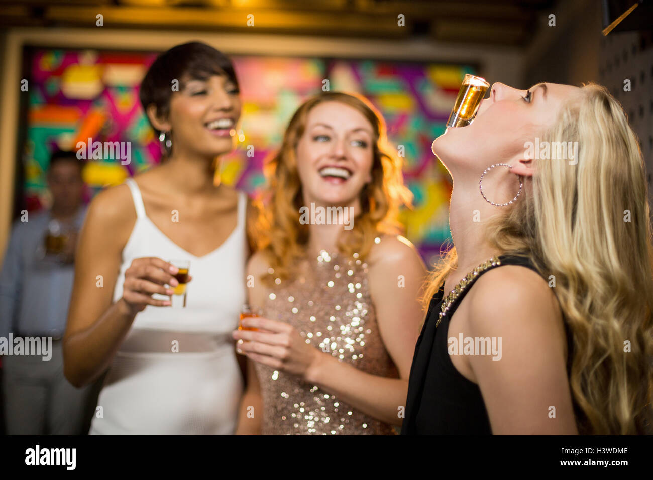 Woman balancing a shot glass on her mouth - Stock Image