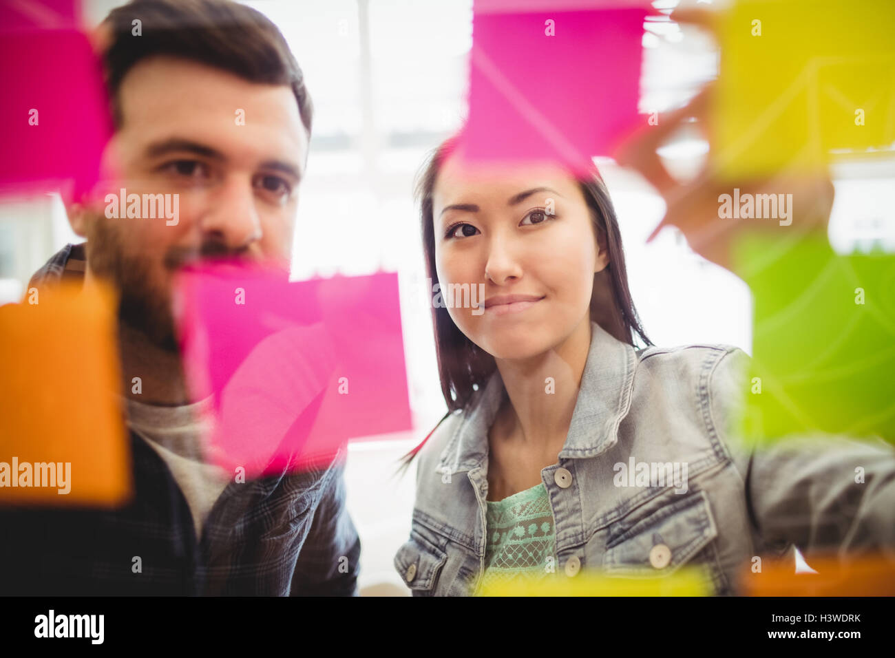 Business people looking at multi colored sticky notes on glass - Stock Image