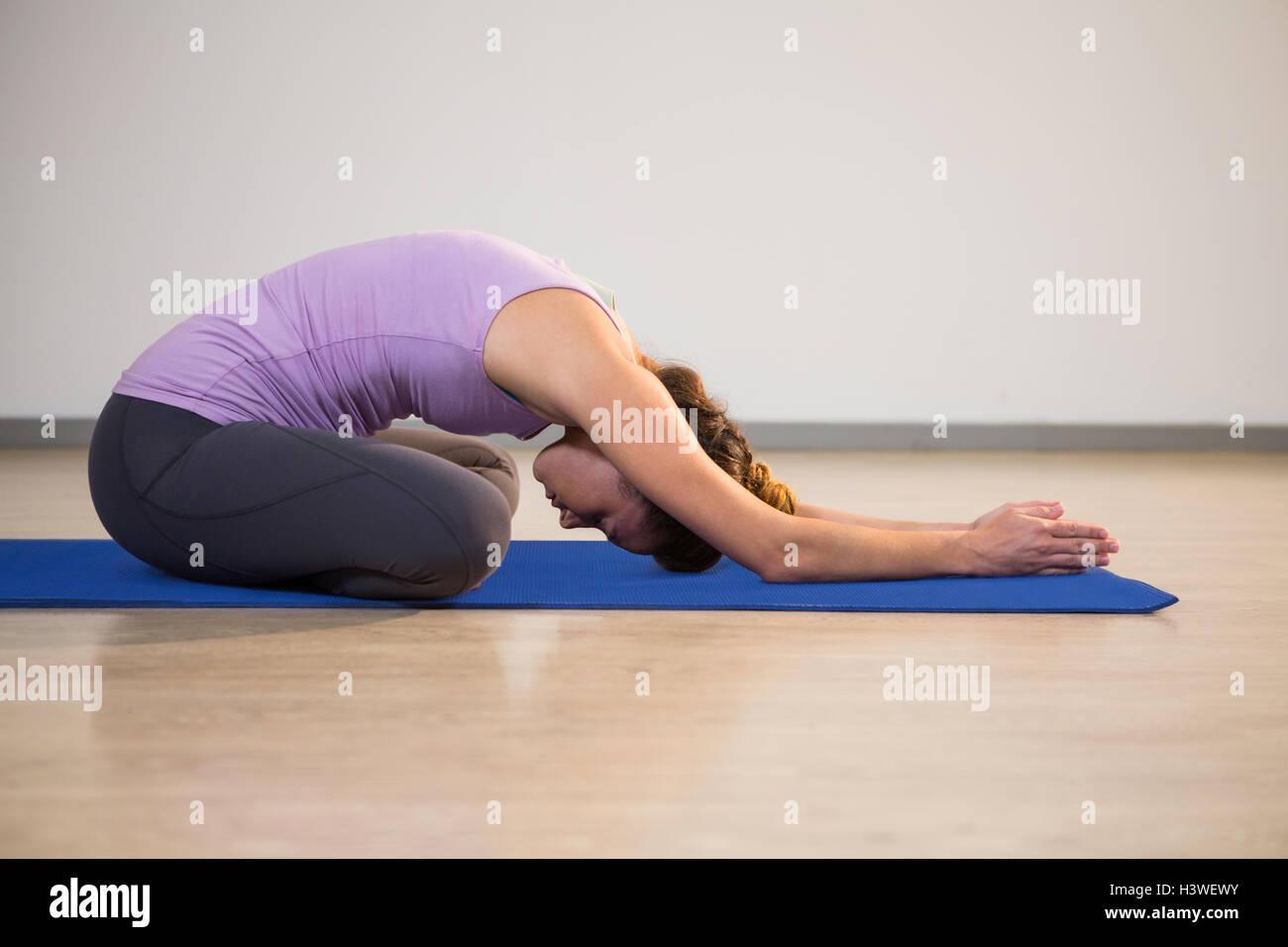 Woman doing yoga child pose on exercise mat Stock Photo