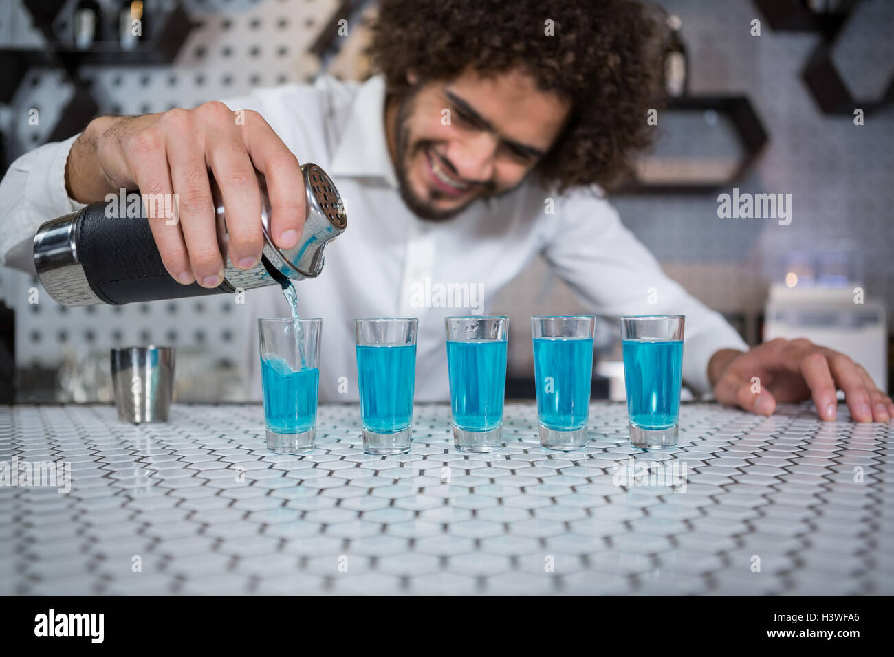 Bartender pouring cocktail into shot glasses - Stock Image