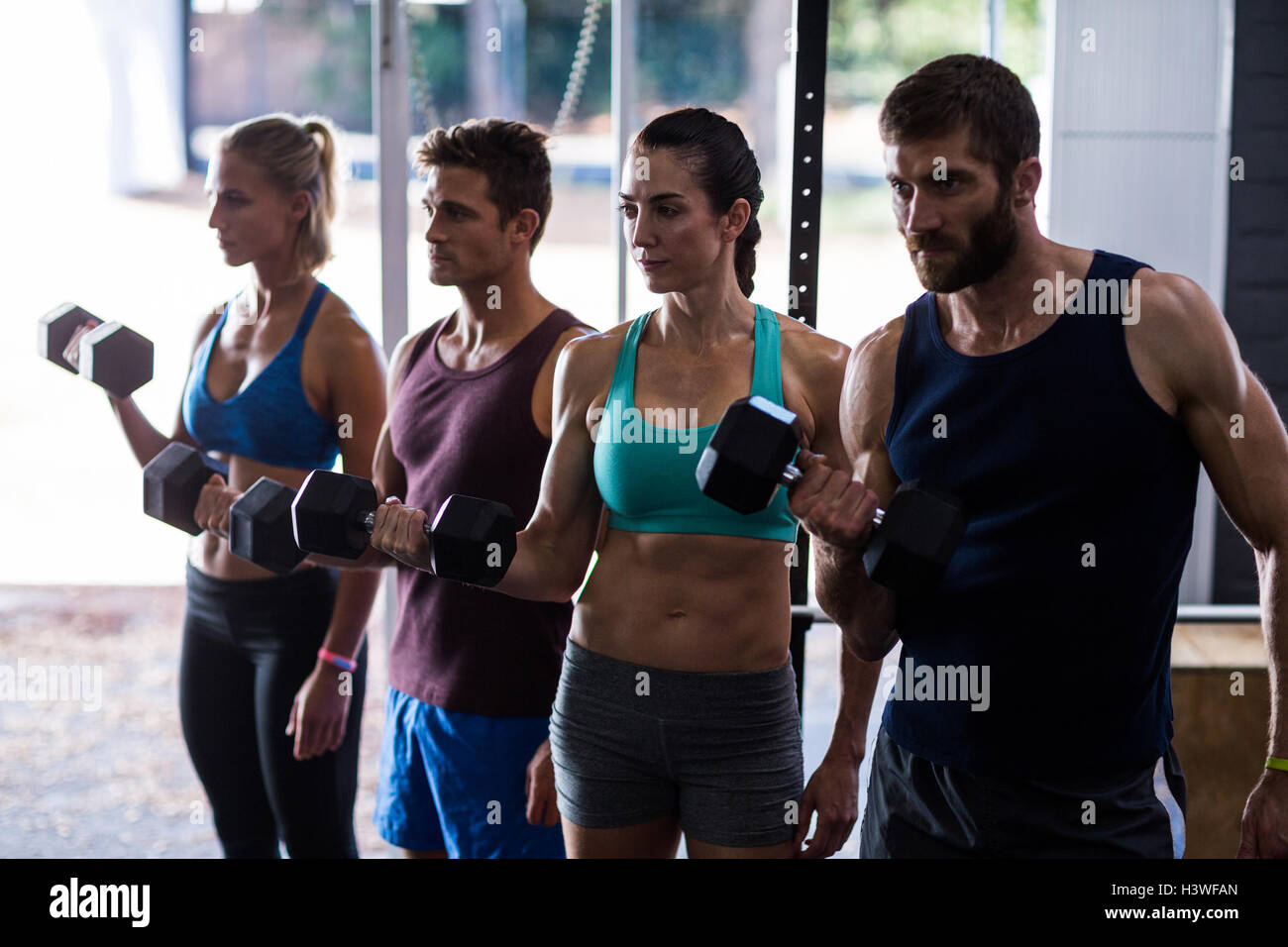 Friends holding dumbbells while working out - Stock Image