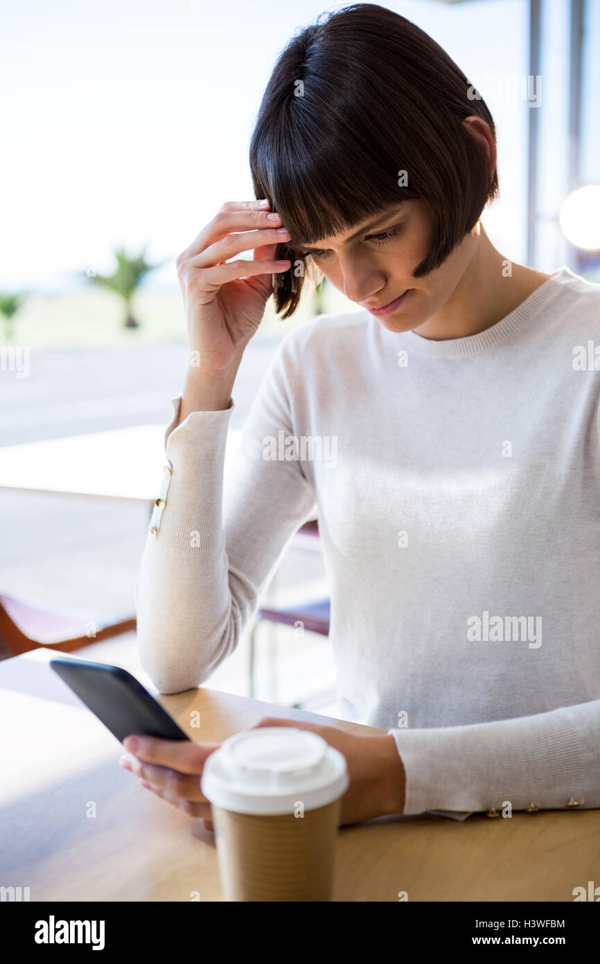 Tense woman using mobile phone - Stock Image
