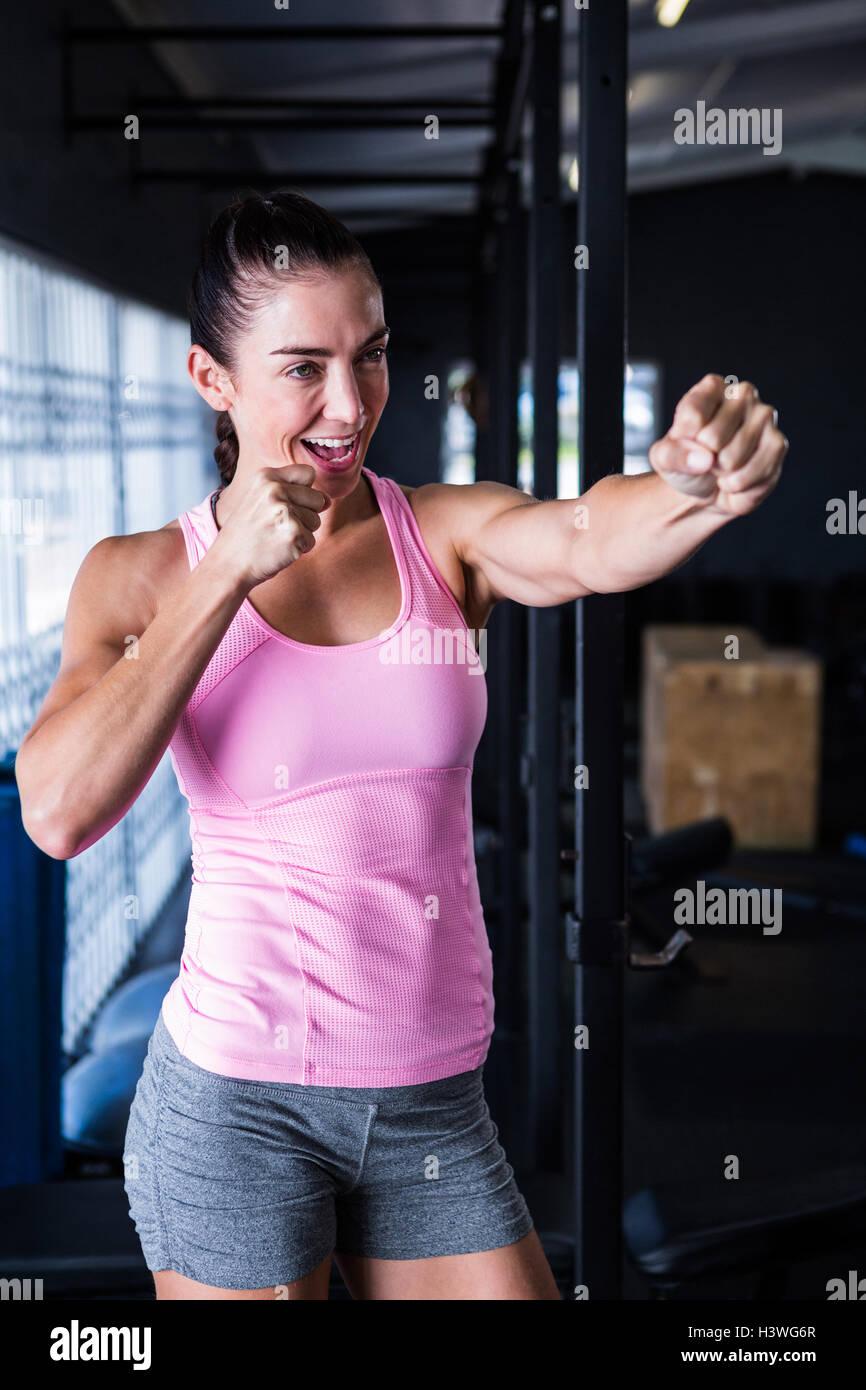 Smiling female athlete punching - Stock Image