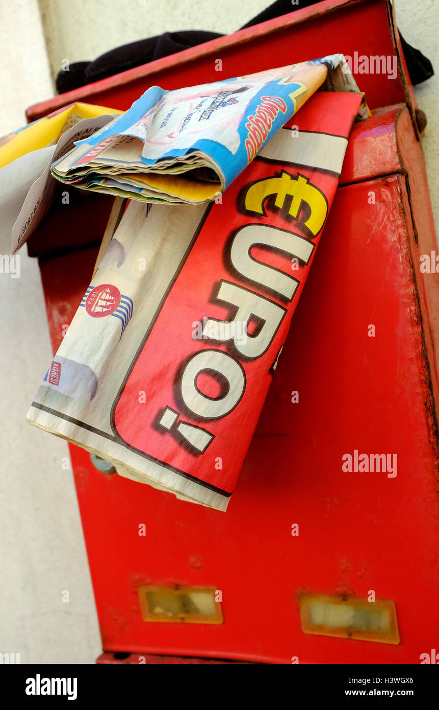 mailers stuffed in red mail box outside house - Stock Image