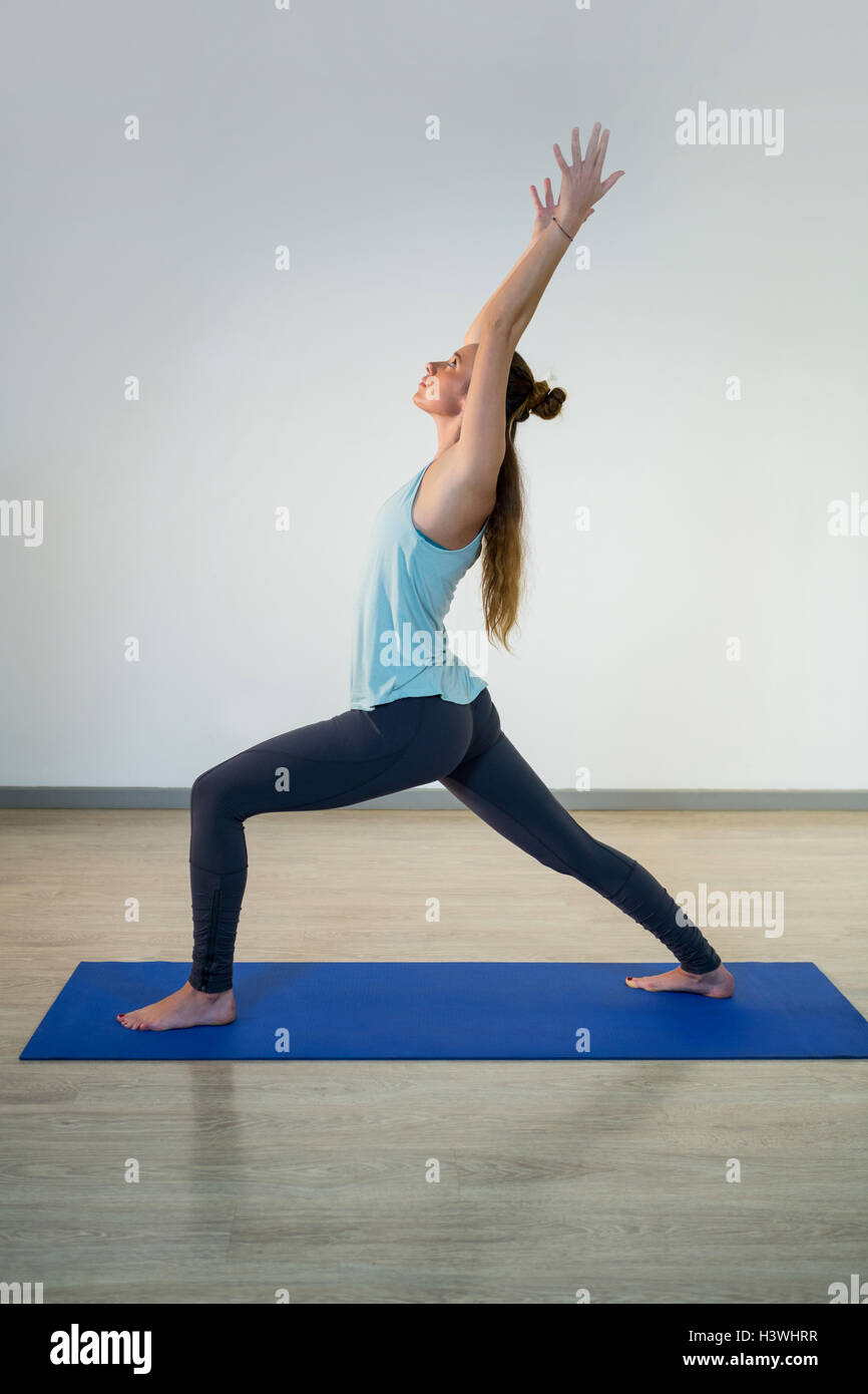 Woman performing warrior pose on exercise mat - Stock Image