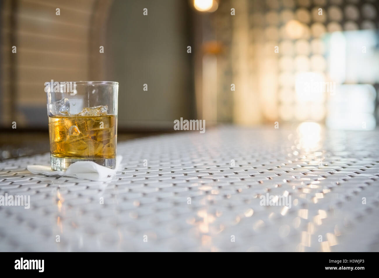 Glass of whisky with ice cube on bar counter - Stock Image