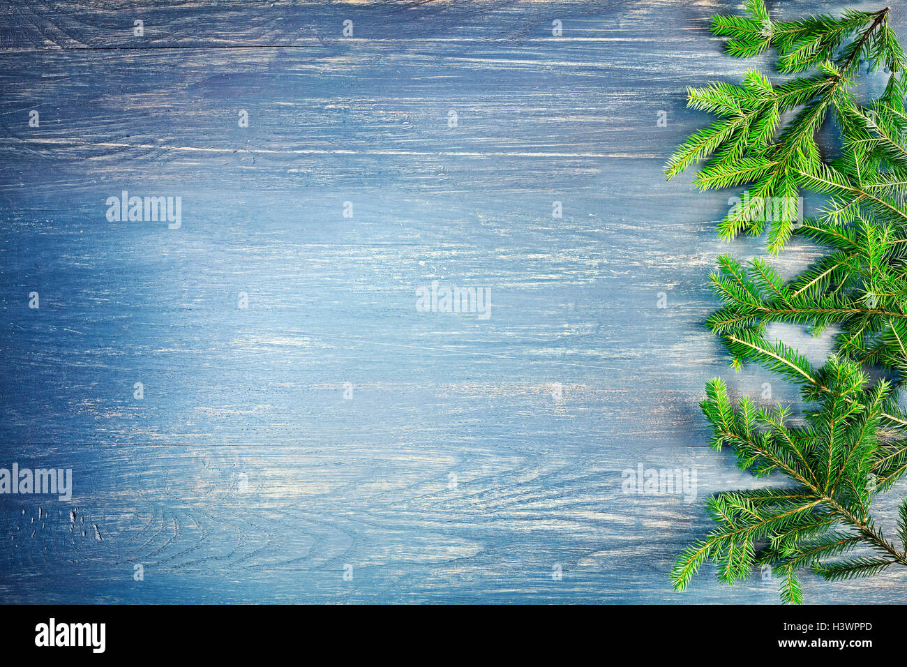 Retro stylized Christmas background with spruce branches on a rustic wooden table, top view with copy space. - Stock Image