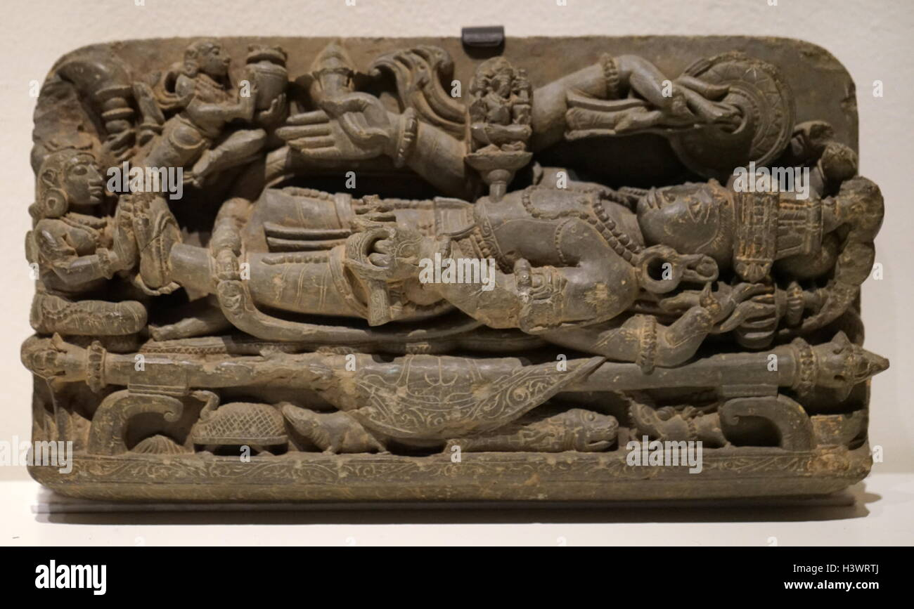 Carved statue of the God Vishnu laying over the cosmic serpent Shesha. Dated 14th Century - Stock Image