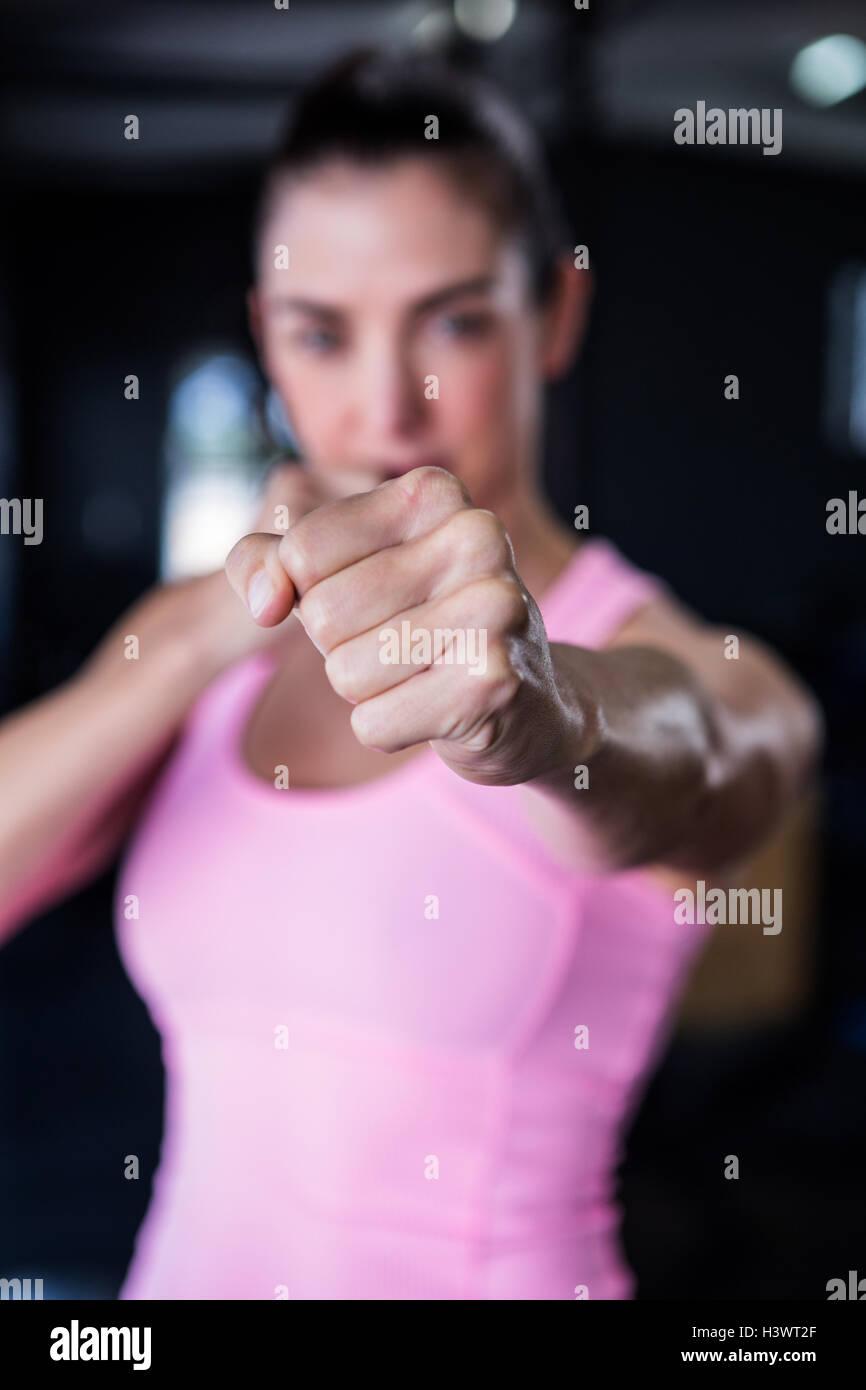 Portrait of female athlete punching - Stock Image