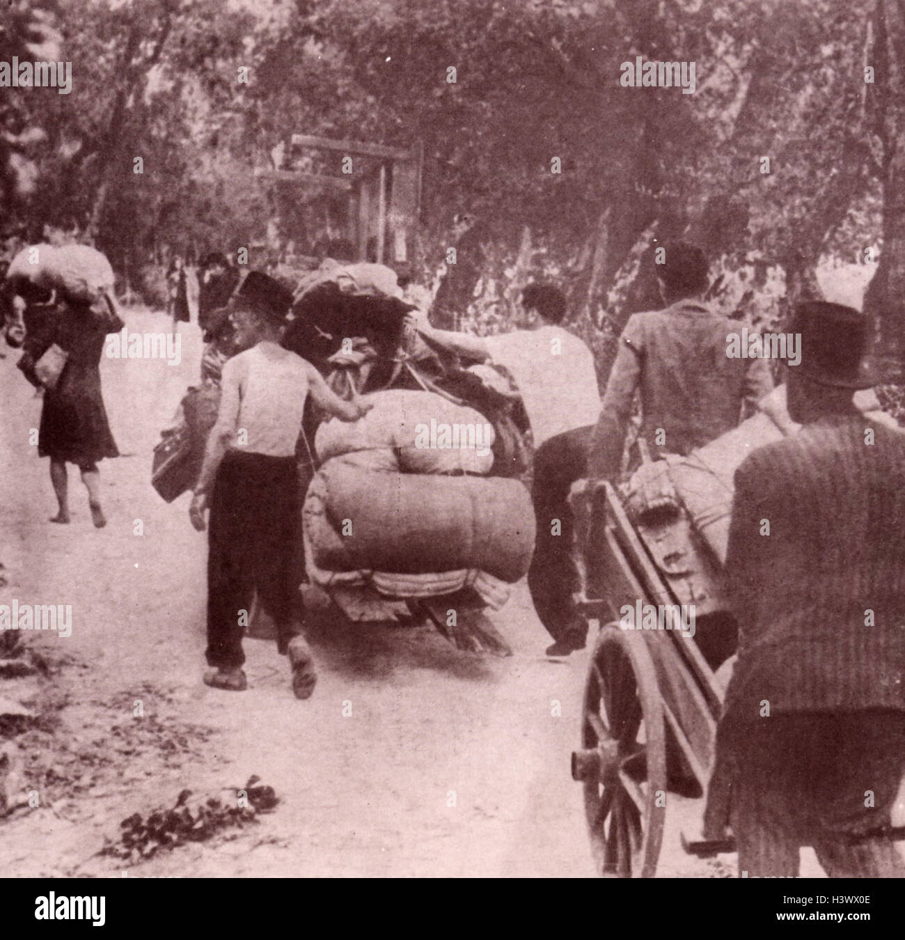 Photograph of Italian refugees towing their possessions after bombings. Dated 20th Century - Stock Image