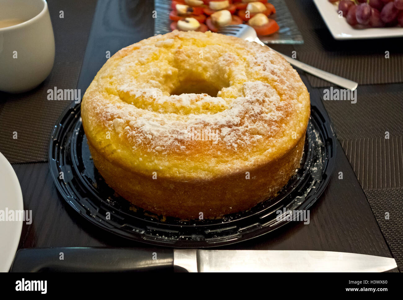 Lemon Bundt cake dusted with icing sugar, on a table for tea. - Stock Image