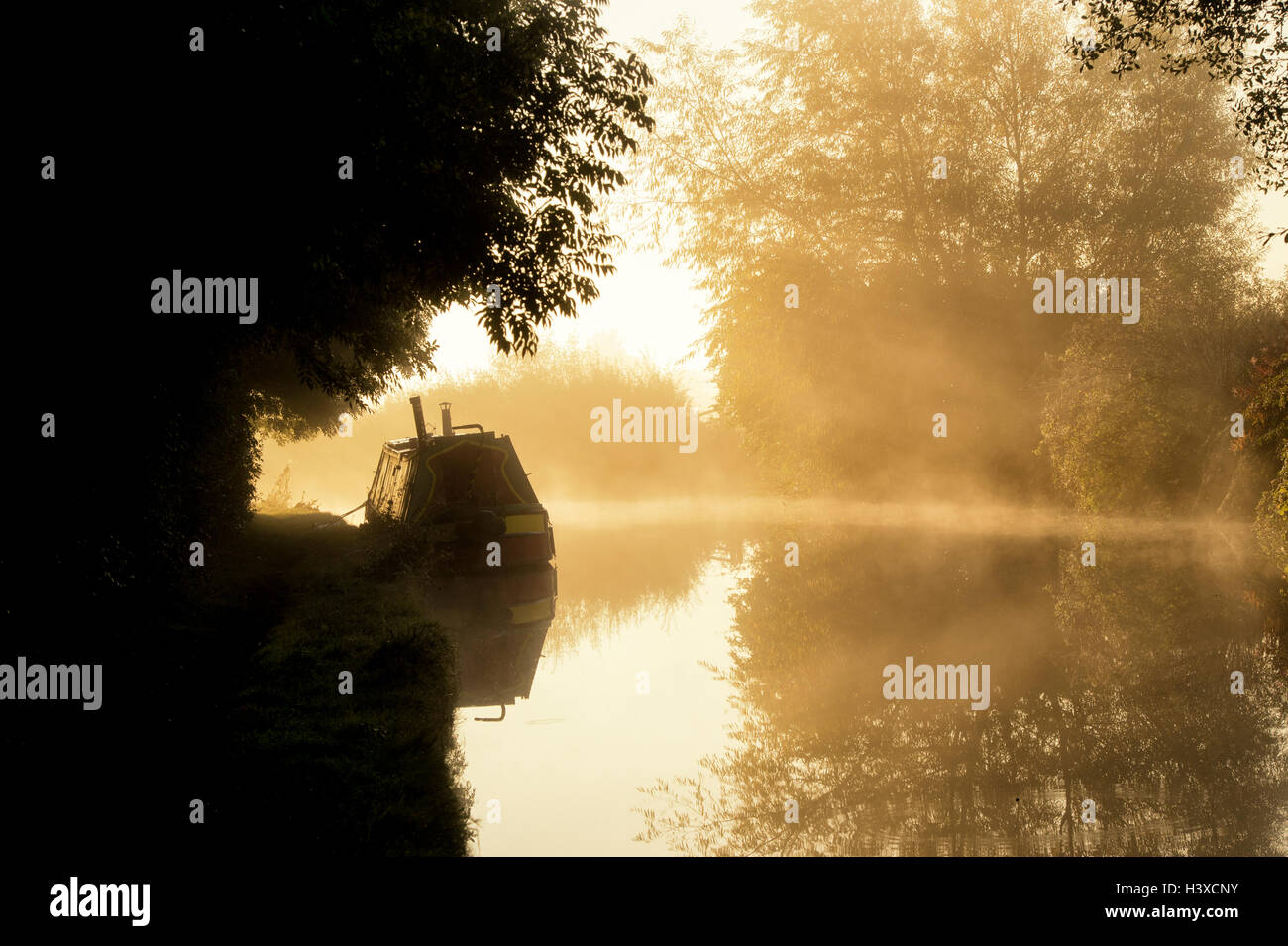 Narrowboat on a misty oxford canal in the early morning. Oxfordshire, England. Silhouette - Stock Image
