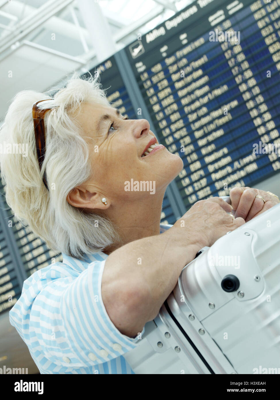 Senior, airport, luggage, travel, information board, happy, smile, portrait, side view, airport hall, information - Stock Image