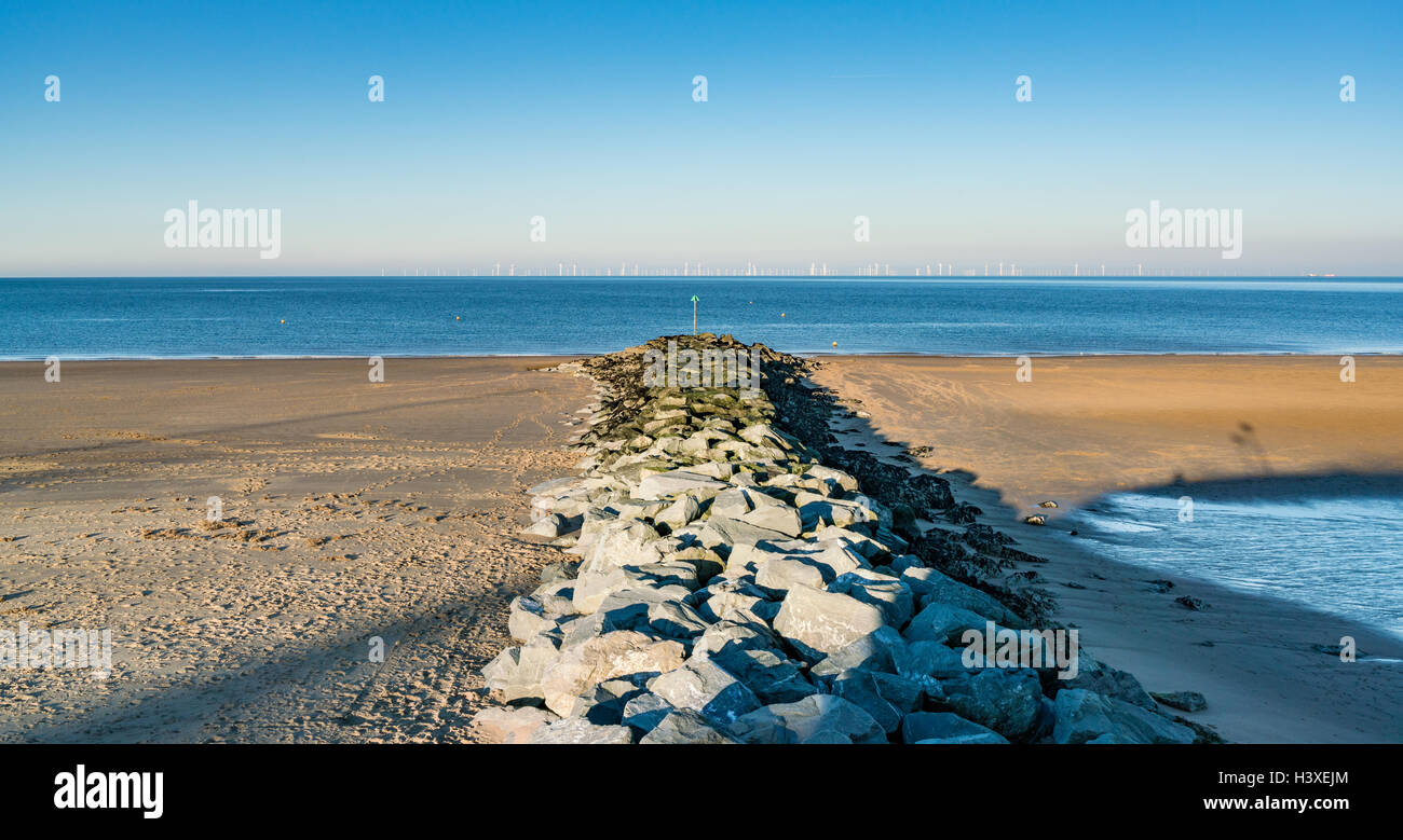 Breakwater on Colwyn Bay Beach points to offshore wind turbines - Stock Image