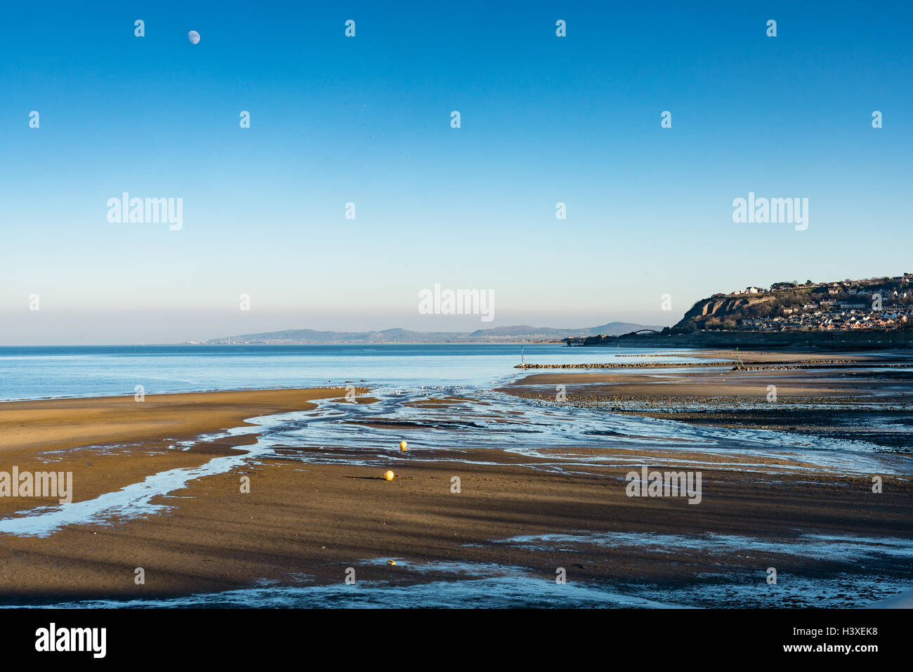 Tidal streams on Colwyn Bay beach looking along the coast towards Rhyl - Stock Image