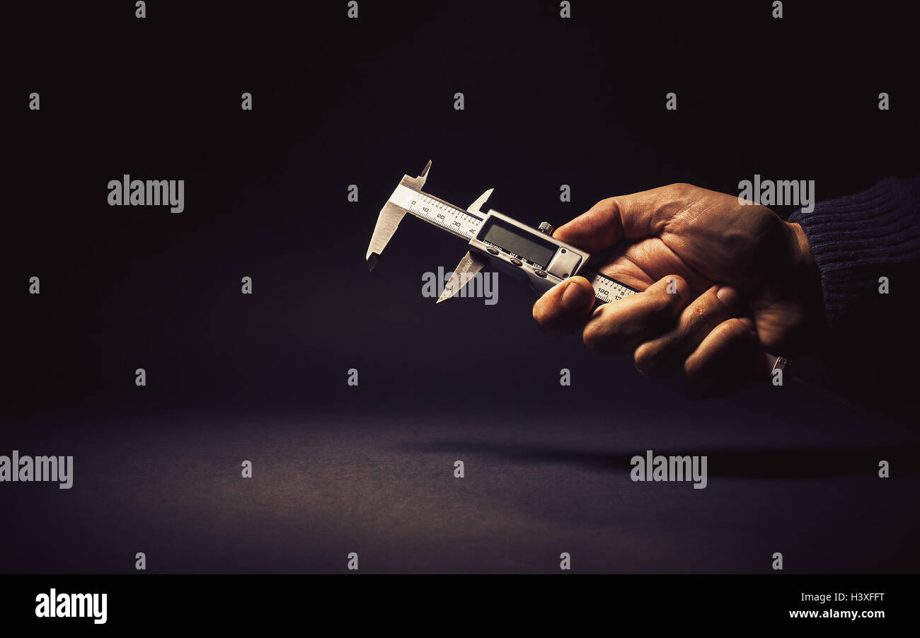 Vernier caliper in male hand, conceptual composition about precise measuring. - Stock Image