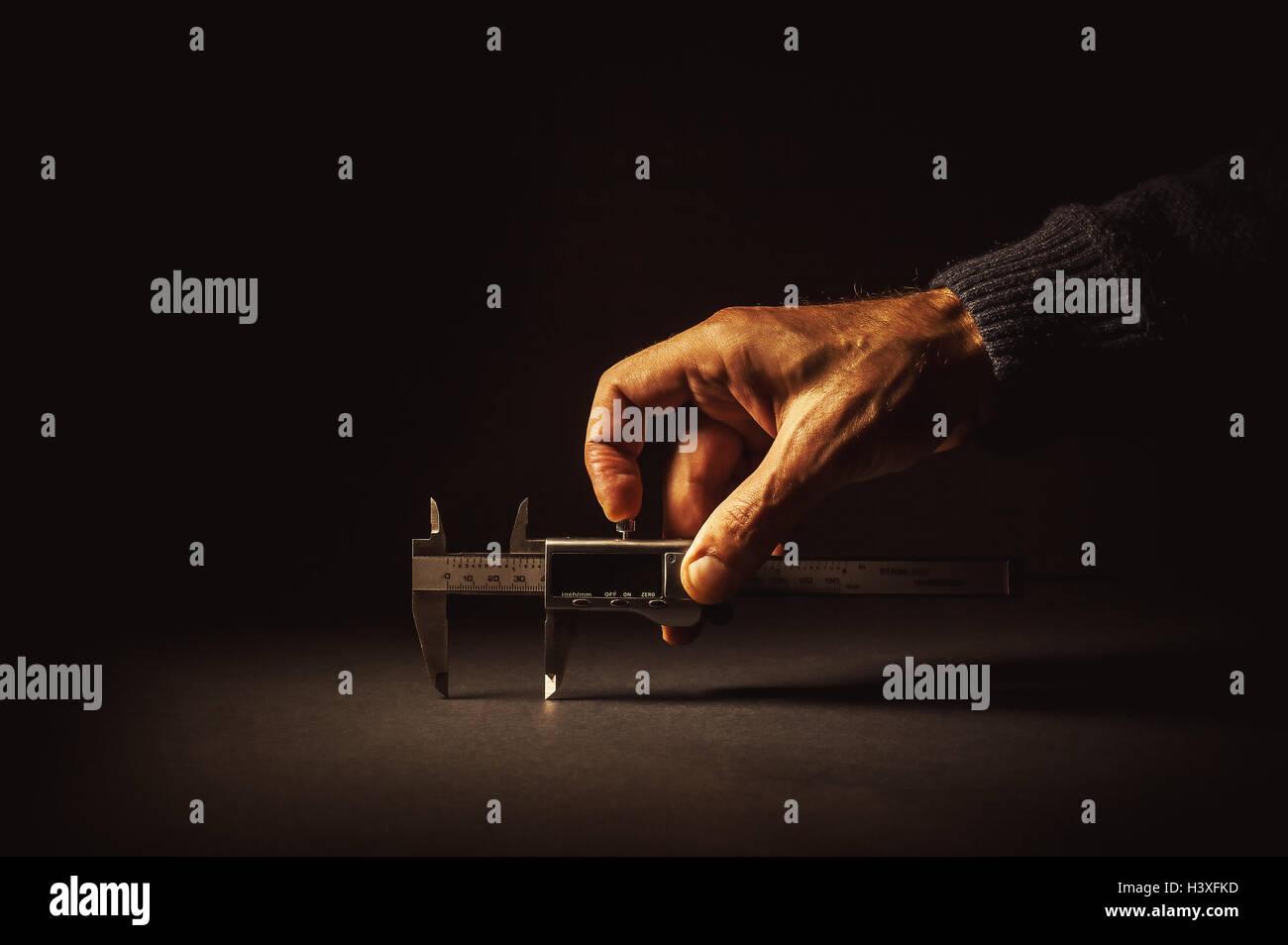 Measuring something with vernier caliper tool, on dark surface. - Stock Image