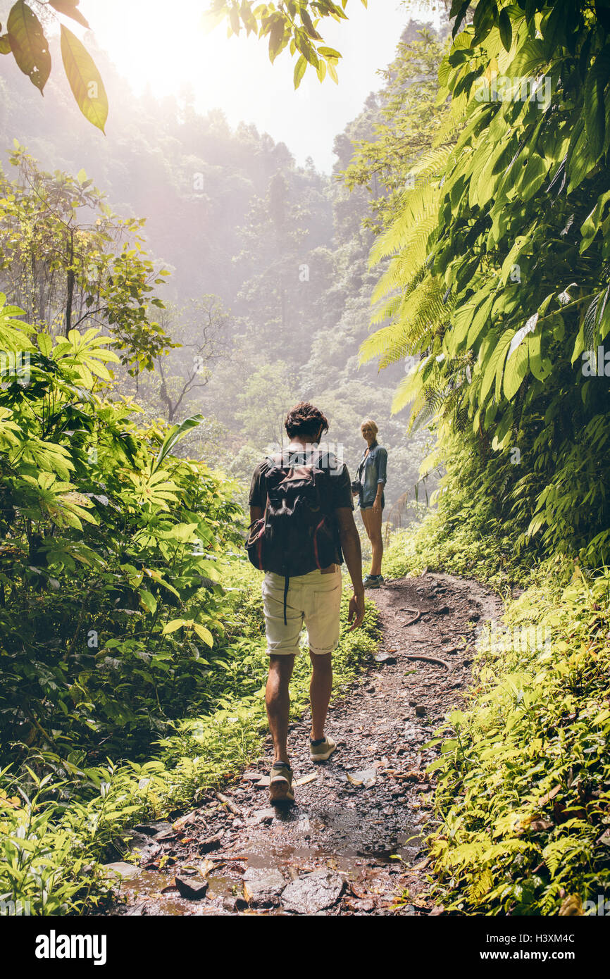 Rear view shot of young couple walking along a path through the tree. Man and woman hiking on forest trail. - Stock Image